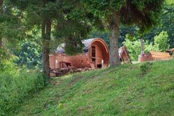 Outdoor wooden barrel sauna in the garden.