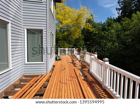 Outdoor wooden deck being remodeled with new red cedar wood floor boards being installed     Photo stock ©