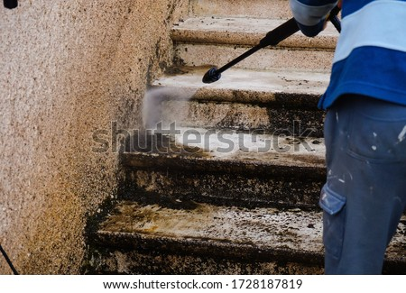 Outdoor work : a maintenance officer cleans and defoams a dirty exterior stone staircase with the lance of a high-pressure washer, while the bad water, charged with moss, trikles down the steps Stock photo ©
