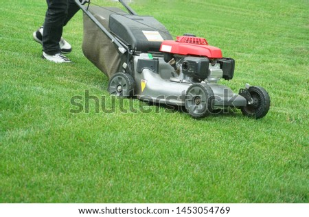 outdoor worker working on mowing the lawn  #1453054769