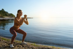 Outdoor Workout. Young woman doing deep squat exercise on the beach, copy space