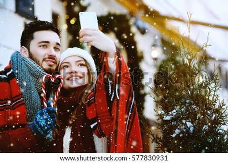 Outdoor. Young beautiful happy smiling couple posing on street, making selfie. Models bundled up in tartan blanket, holding candy canes. Snowfall, fir-trees on background. Empty, copy space for text