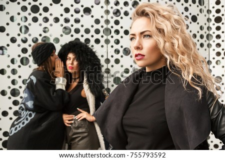 Outdoors fashion portrait of two girlfriends gossiping about third. To dissolve gossip. Discussing a friend.To envy a more beautiful girlfriend. Wearing stylish outerwear and hats. Bright make up - Shutterstock ID 755793592