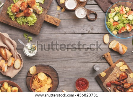 Outdoors Food Concept. On the wooden table different food with copy space, grilled chicken legs, buffalo wings, bread, salad, potatoes, potato chips and beer - Shutterstock ID 436820731