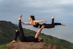 Outdoors full length portrait young attractive and concentrated couple of yoga acrobats practicing acroyoga. Sportswoman lying on mans hands. Balancing and meditation exercise on the edge of Earth.