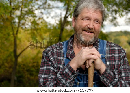 outdoors guy in plaid shirt & dungarees leans on shovel handle