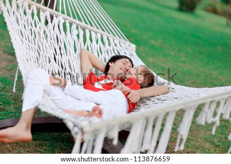outdoors in a white hammock resting father and son in red shirts