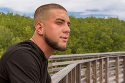Outdoors leaning on the boardwalk rail, he looks across the way with a staring gaze. A scared face tough guy with a military buzz cut leans on the wood rail with a focused look.