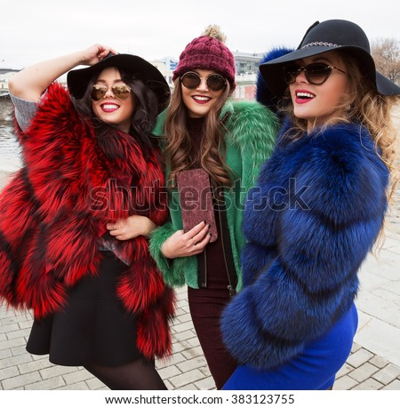 Outdoors lifestyle fashion portrait of company pretty cheerful girls best friends in stylish hats and sunglasses. Wearing bright colored fur coats. Smiling and walking on the city. Close up