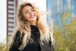 Outdoors lifestyle fashion portrait of happy stunning blonde girl. Beautiful smile. Walking to the city street. Long curly light hair. Wearing stylish black coat. Joyful  and cheerful woman. Happiness