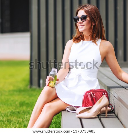 Outdoors lifestyle fashion portrait of pretty red hair girl sitting on the bench. Drinking natural lemonade. Enjoing sunny day, resting. Wearing stylish white dress, sunglass. Shoeless. Rest for feet #1373733485