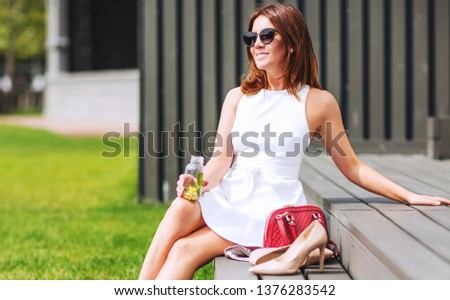Outdoors lifestyle fashion portrait of pretty red hair girl sitting on the bench. Drinking natural lemonade. Enjoing sunny day, resting. Wearing stylish white dress, sunglass. Shoeless. Rest for feet #1376283542