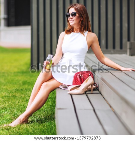 Outdoors lifestyle fashion portrait of pretty red hair girl sitting on the bench. Drinking natural lemonade. Enjoing sunny day, resting. Wearing stylish white dress, sunglass. Shoeless. Rest for feet #1379792873