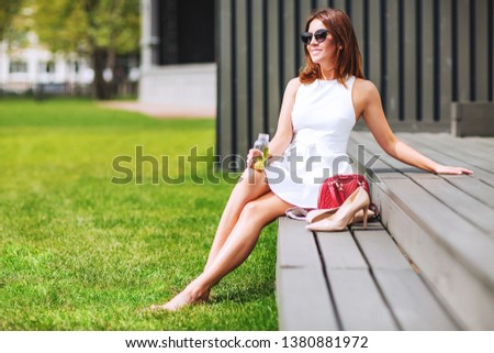Outdoors lifestyle fashion portrait of pretty red hair girl sitting on the bench. Drinking natural lemonade. Enjoing sunny day, resting. Wearing stylish white dress, sunglass. Shoeless. Rest for feet #1380881972