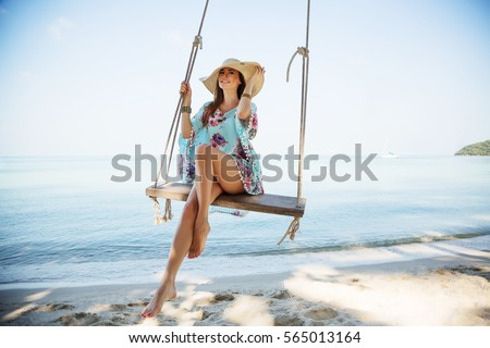 Outdoors lifestyle fashion portrait stunning young girl enjoying on swing on the tropical island. In the background the sea. Wearing stylish blue dress, straw hat and bracelets. Straight long hair