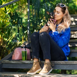 Outdoors lifestyle portrait of pretty girl sitting on the wooden stair in the tropical garden. Hugging and kissing small cute dog. Wearing stylish  jeans, pantone jacket. Relaxing, enjoying life