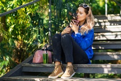 Outdoors lifestyle portrait of pretty girl sitting on the wooden stair in the tropical garden. Hugging and kissing small cute dog. Wearing stylish  jeans, pantone color jacket. Relaxing, enjoying life