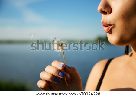 Outdoors lifestyle portrait of pretty woman. Girl blowing on a dandelion. Smiling and enjoying life on the nature weekend. Walking of the natural park. Freedom and happiness concept.