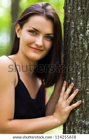 Outdoors portrait of a happy young woman leaning on tree trunk in forest