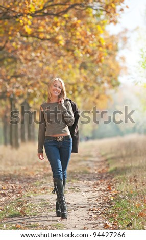 Outdoors portrait of a pretty smiling blond woman in the autumn park
