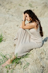 Outdoors portrait of a stunning girl sitting on the sand at the beach.