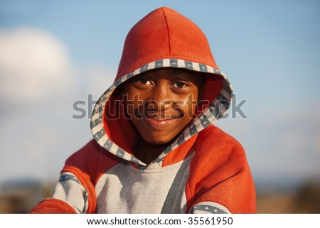 outdoors portrait of African child with red blouse with hood, golden hour, blue sky background