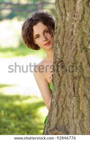 outdoors portrait of beautiful young curly woman looking from behind the tree trunk