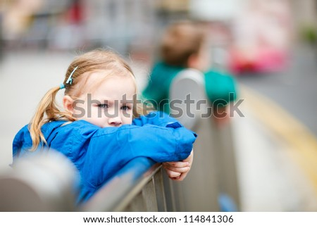 Outdoors portrait of cute little girl in a city