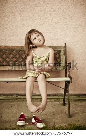 Outdoors portrait of small cute child with hanging legs - sepia tone - stock photo