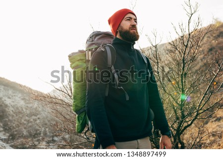 Outdoors portrait of young man looking to the horizon in mountains with travel backpack and red hat. Traveler bearded male relaxing after trekking during journey. Travel, lifestyle, sport
