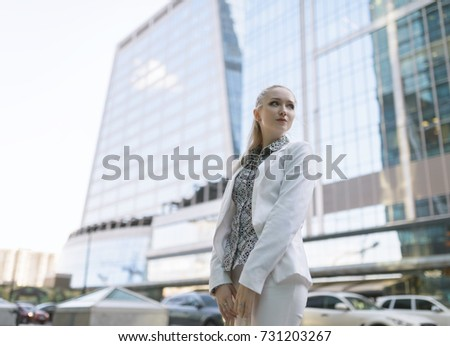 Outdoors portrait of young woman in white jacket.