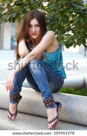 Outdoors street portrait of beautiful young brunette girl near tree