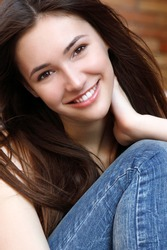 Outdoors street portrait of beautiful young brunette smiling teen girl