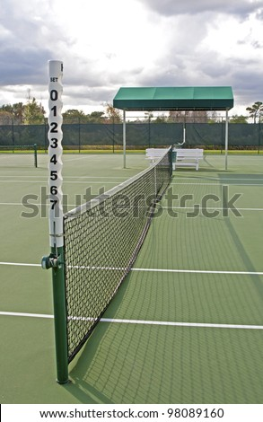 Outdoors tennis court and close up of net on a sunny and cloudy day