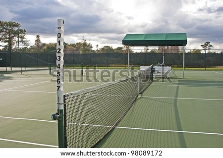 Outdoors tennis court on a sunny and cloudy day.