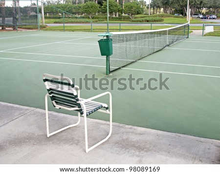 Outdoors tennis court on a sunny day, with a chair in the foreground.