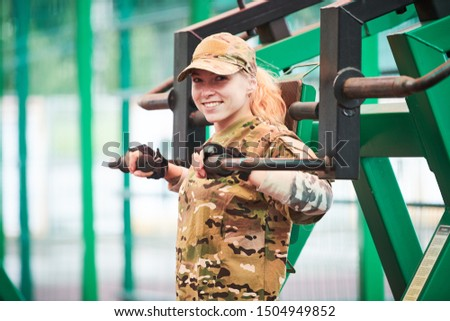 outdoors training . military woman workouts on weight machine