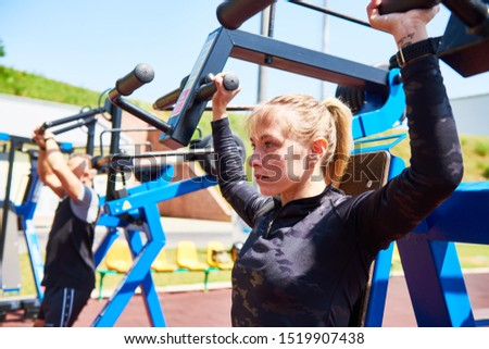 outdoors training . woman workouts on weight machine
