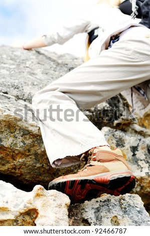outdoors woman climbs a rock while hiking and exploring