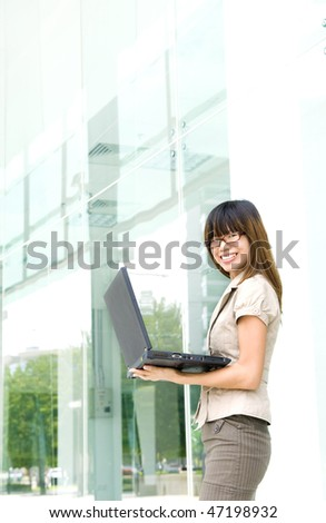 Outdoors work. Asian female with laptop outside a modern building.