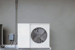Outer air conditioner coil with hot draining fan, attached at gray concrete building wall