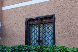 Outer window of home opening outside, outer window is covered with iron fence