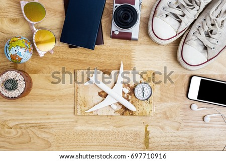 Outfit and accessories of traveler on blue background with copy space, Travel concept.Overhead view of Traveler's accessories, Essential vacation items, Travel concept on wooden background. top view  - Shutterstock ID 697710916