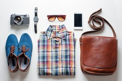 Outfit of traveler, student, teenager. Overhead of essentials for modern young person. Different objects on white wooden background.