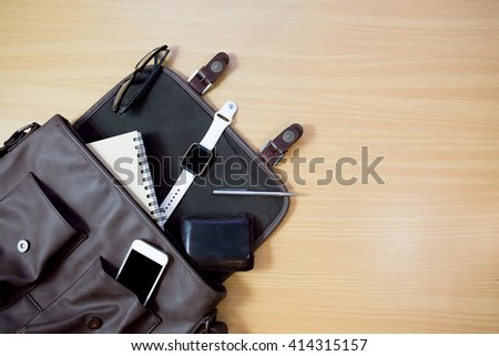 Outfit of traveler, student, teenager, young man.  Different objects on wooden background: leather bag, smart watch,smartphone, glasses, notebook and pen top view . retro style ,vintage tone