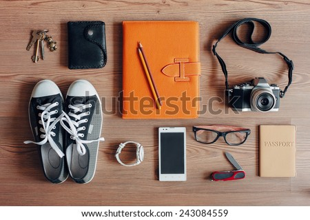 Outfit of traveler, student, teenager, young woman or guy. Overhead of essentials for modern young person. Different objects on wooden background.