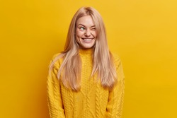Outgoing blonde woman has fun and winks eye dressed in knitted sweater poses against vivid yellow background. Joyful millennial girl smiles with teeth makes funny grimace stands indoor alone