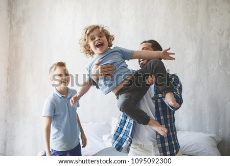 Outgoing dad throwing up beaming child. Positive older brother looking at them. Optimistic dad having fun with sons concept