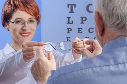 Outgoing female ophthalmologist gives eyeglasses to senior man. View from the back against a visual test with letters. Concept of appointment at the clinic. Selected focus on hands