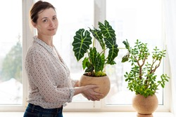 Outgoing smiling woman holding ceramic rounded pot with Alocasia Polly, Amazonian Elephant Ear near the window. Indoor potted fresh plants on the windowsill in the sunlight.